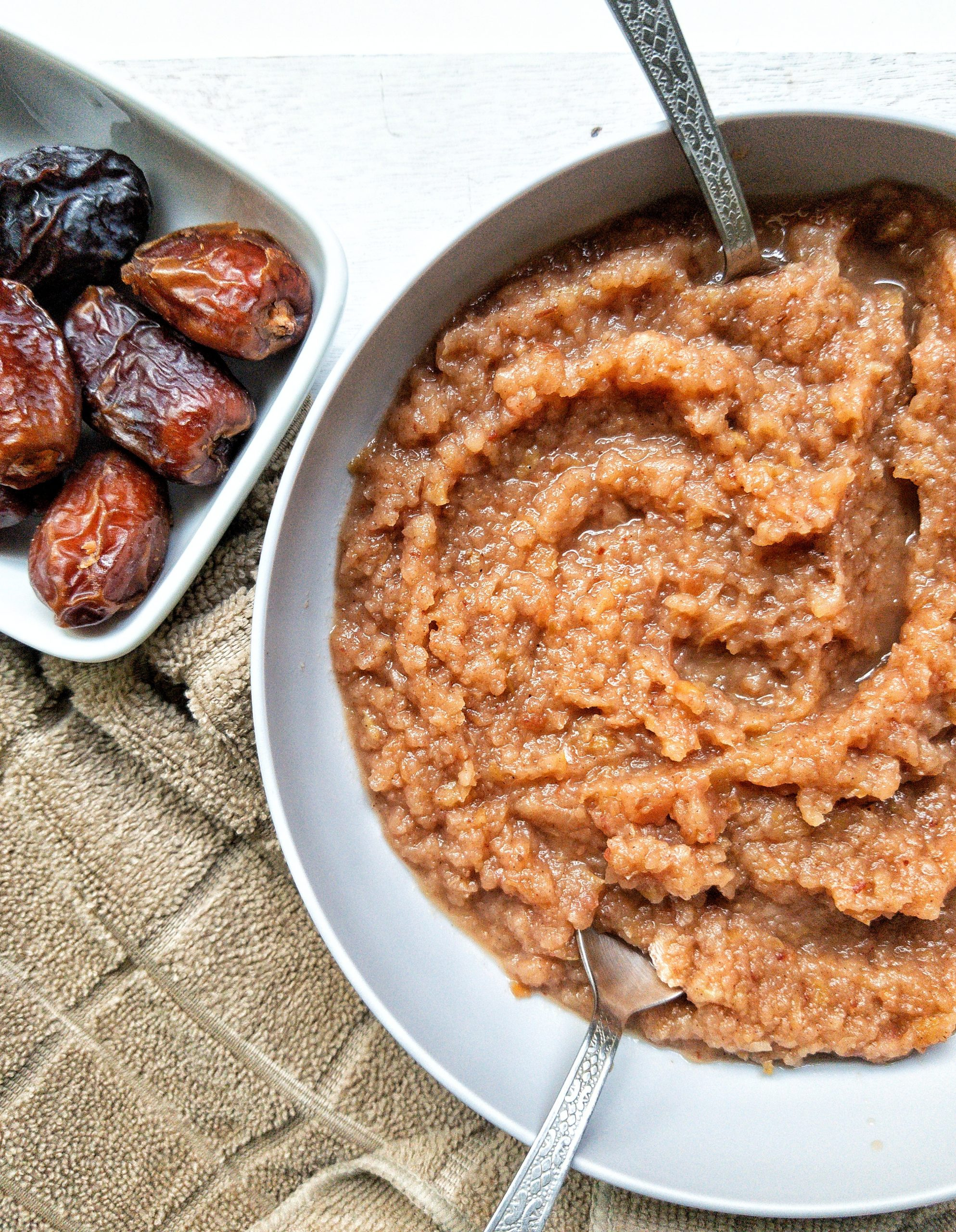 Homemade vegan applesauce in a large bowl with a side of dates
