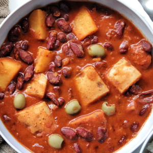 Habichuelas guisadas or Puerto Rican bean stew made with potatoes, beans, and green olives in a bowl.