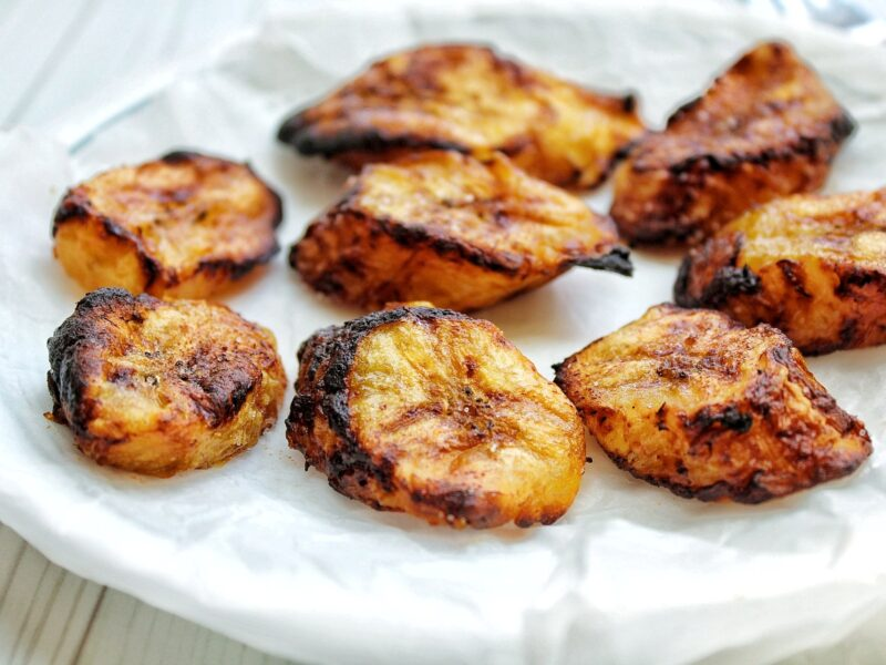 Baked sweet plantains on a plate lined with parchment paper