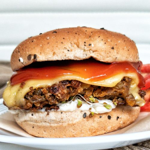 Plant-based lentil burger sprouts, vegan mayo, vegan cheese, tomatoes, and tomato sauce, on a burger bun