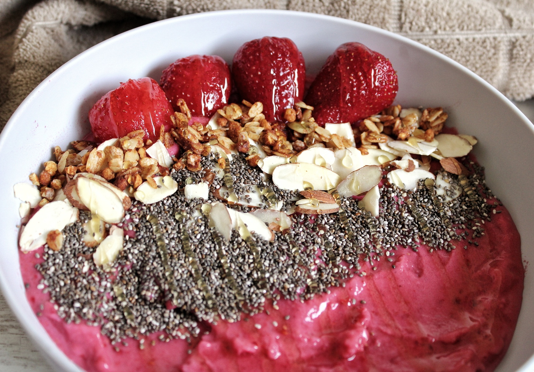 Strawberry raspberry smoothie bowl topped with chia seeds, nuts, granola, and honey.
