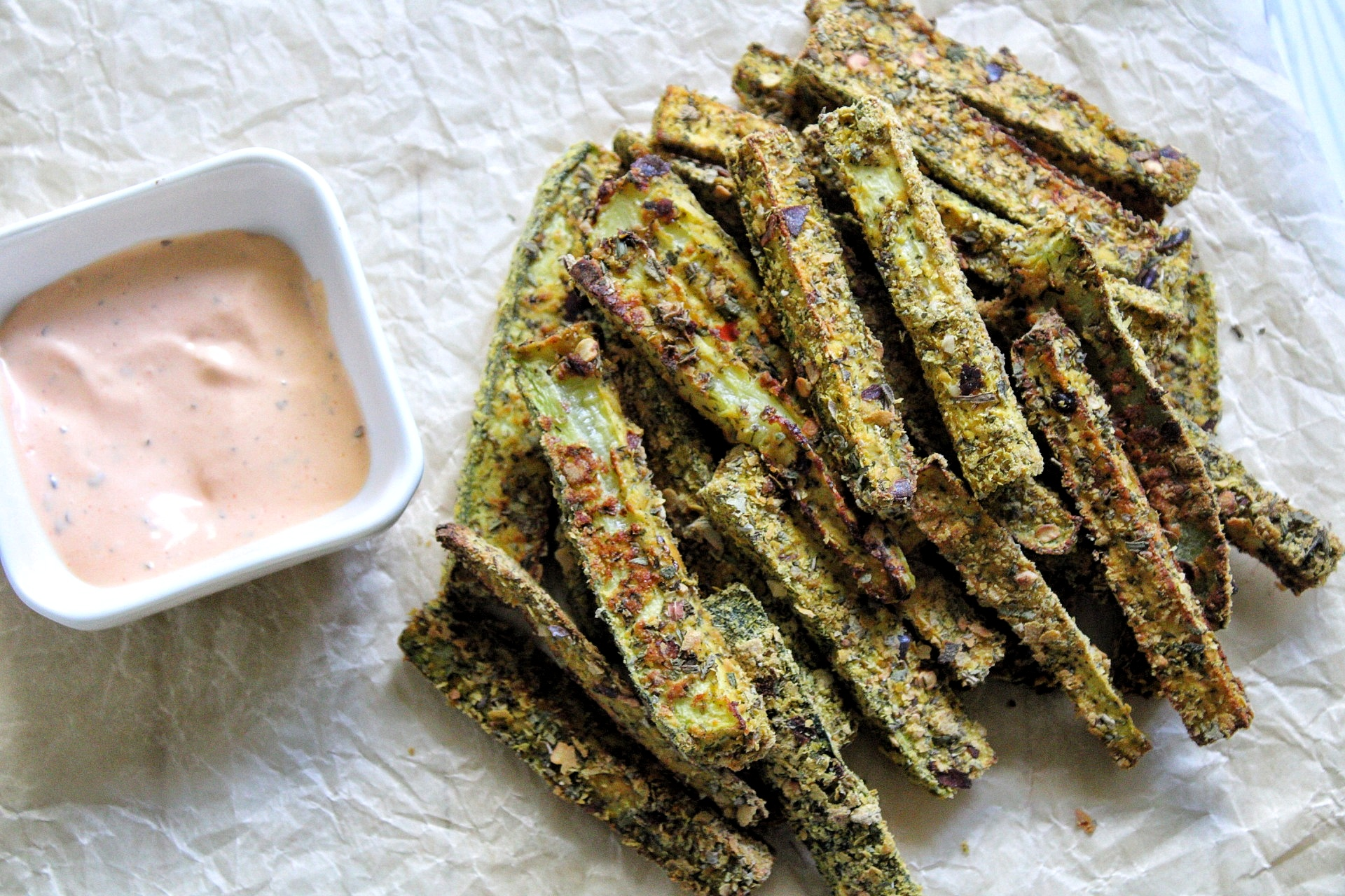 Baked zuchini fries on parchment paper with a side of dipping sauce