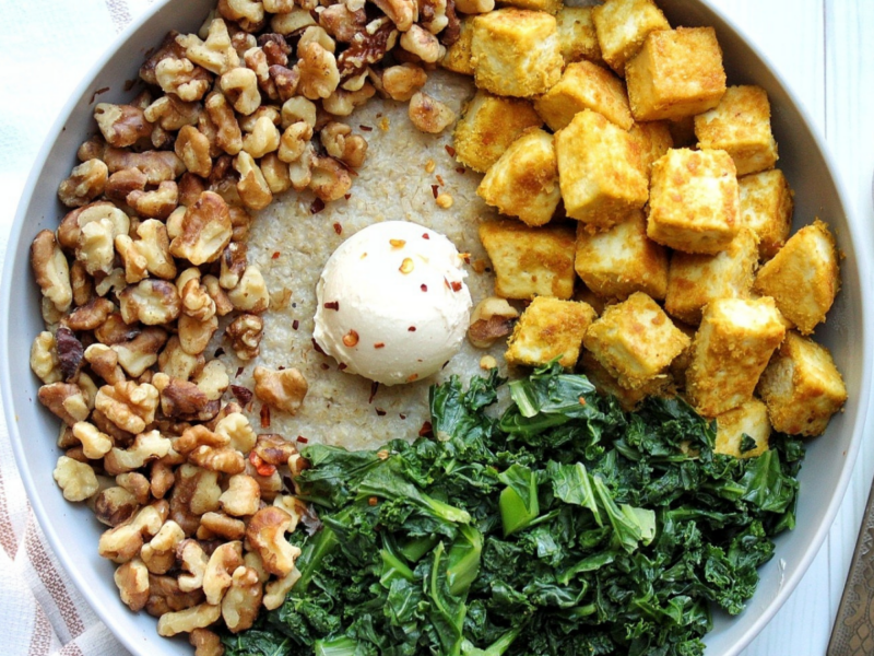 Oat bran in a gray bowl topped with walnuts, kale, tofu, vegan butter, and red chili pepper