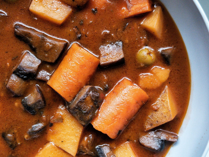 """Puerto Rican vegan beef stew or """"carne guisda"""" in a grey bowl with a side of white rice."""