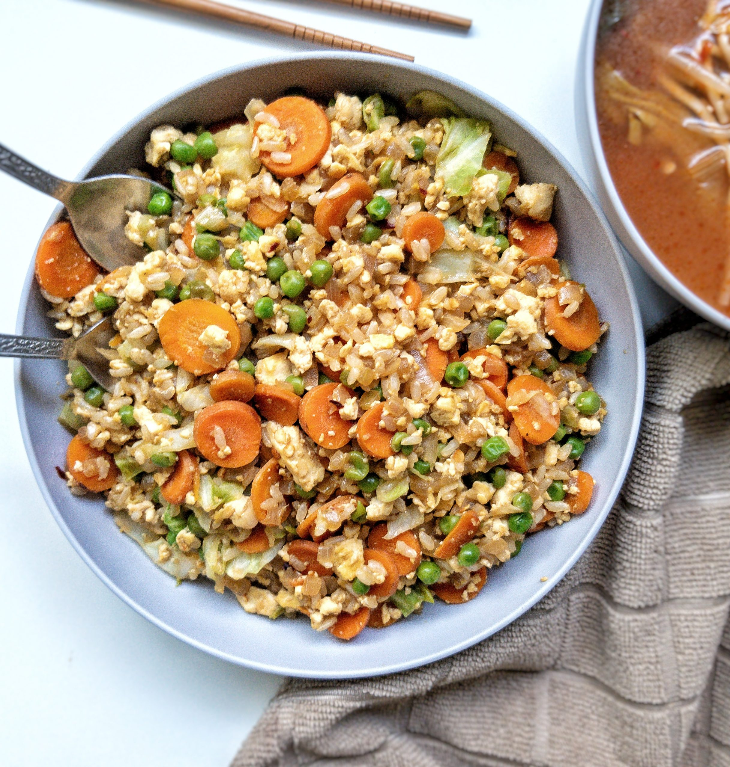 Vegan fried rice with carrots, peas, cabbage, and tofu scramble in a gray bowl
