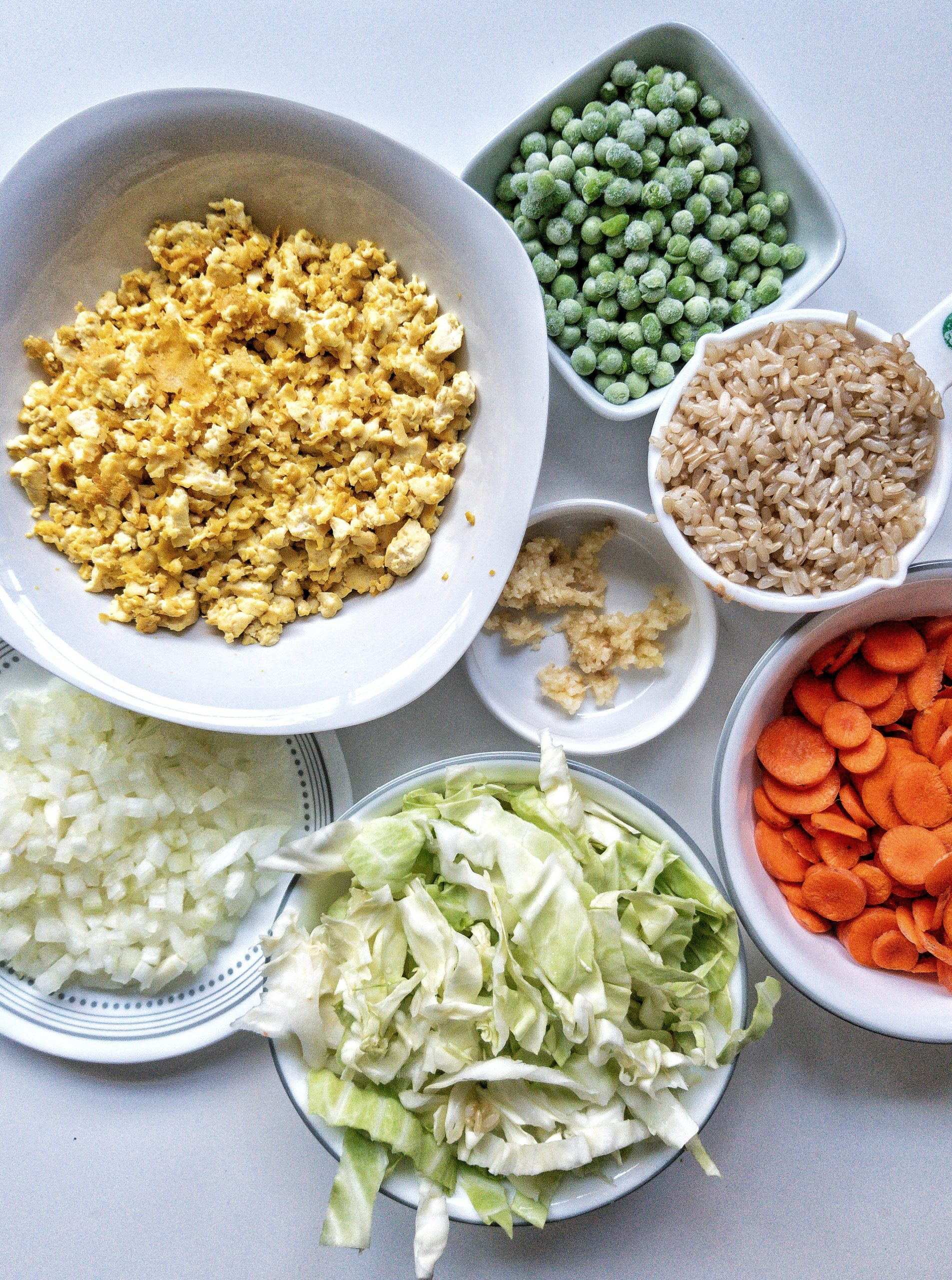 Oil-free, vegan fried rice ingredients including tofu scramble, chopped onion, cabbage, carrots, crushed garlic, frozen peas, and cooked brown rice