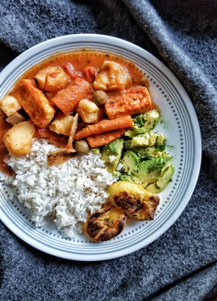 Plate of Puerto Rican tofu guisado with smashed avocado, rice, and plantains
