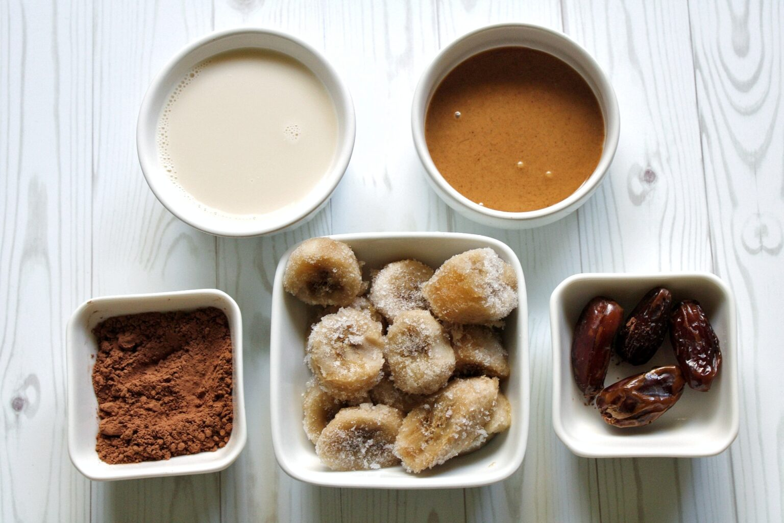 Smoothie ingredients: cocoa powder, frozen bananas, dates, peanut butter, and soy milk.