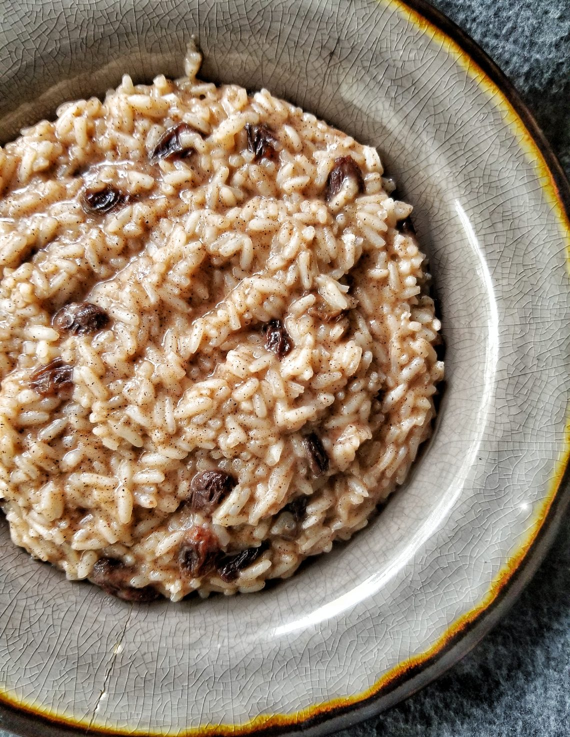 Bowl of warm cinnamon spiced breakfast rice pudding topped with raisins