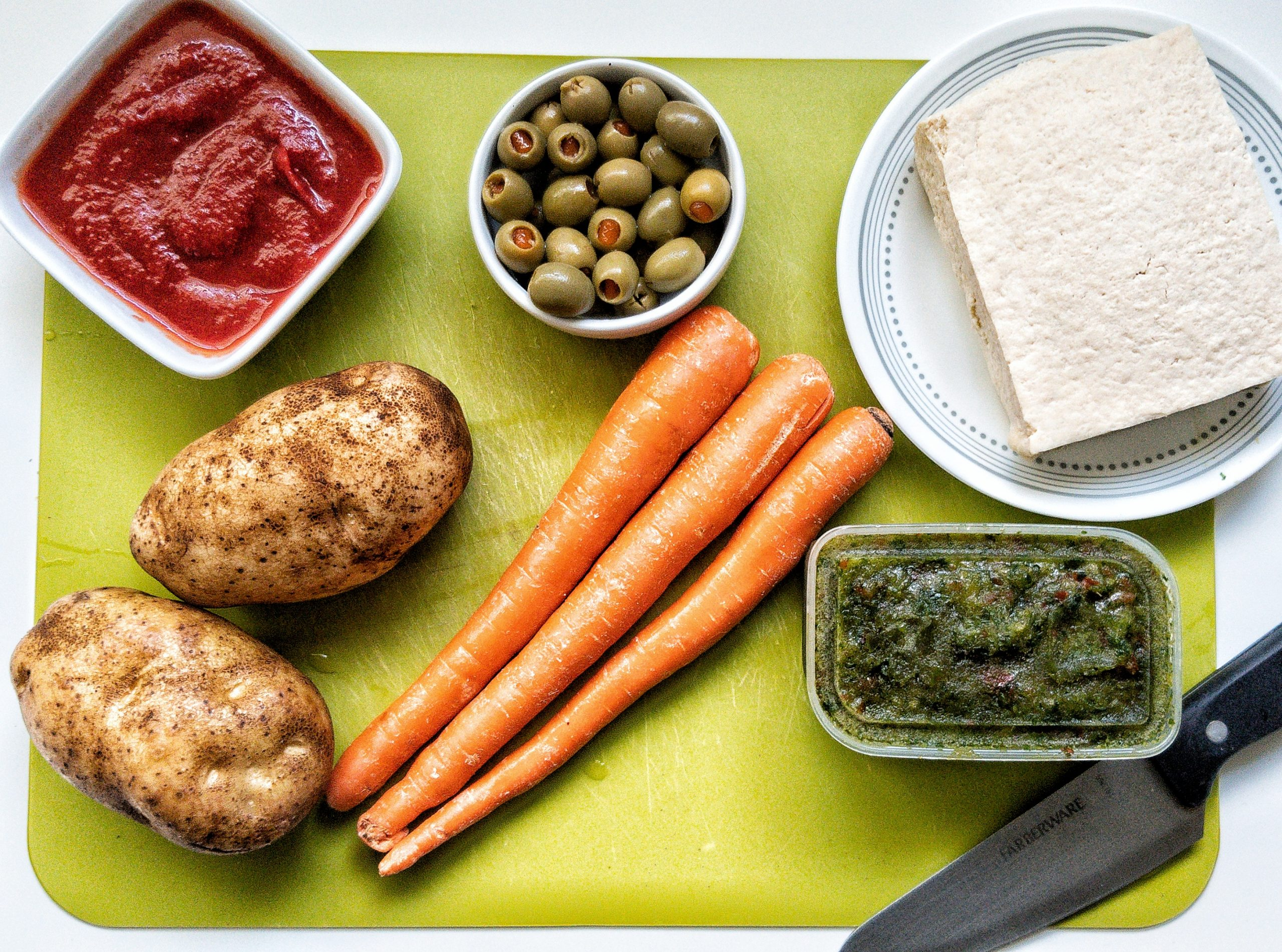 Green chopping board with whole potatoes, carrots, sofrito, tofu block, green Spanish olives, and tomato sauce