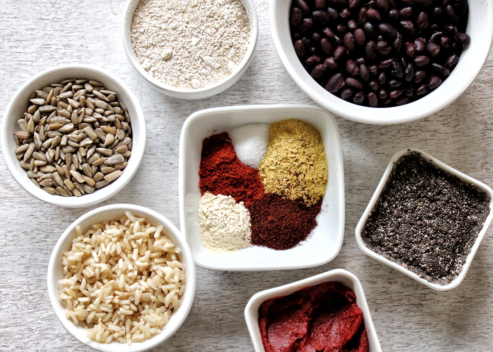 Black beans, oat flour, sunflower seeds, brown rice, tomato paste, chia seeds, and spices