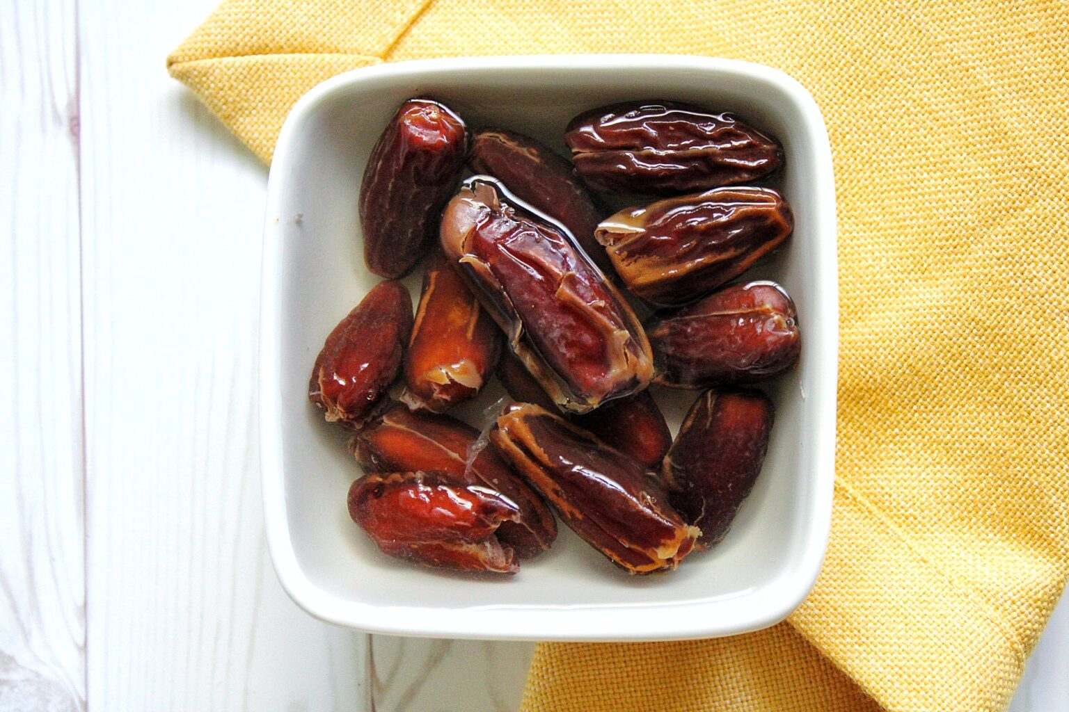 Dates soaking in water in a small dish
