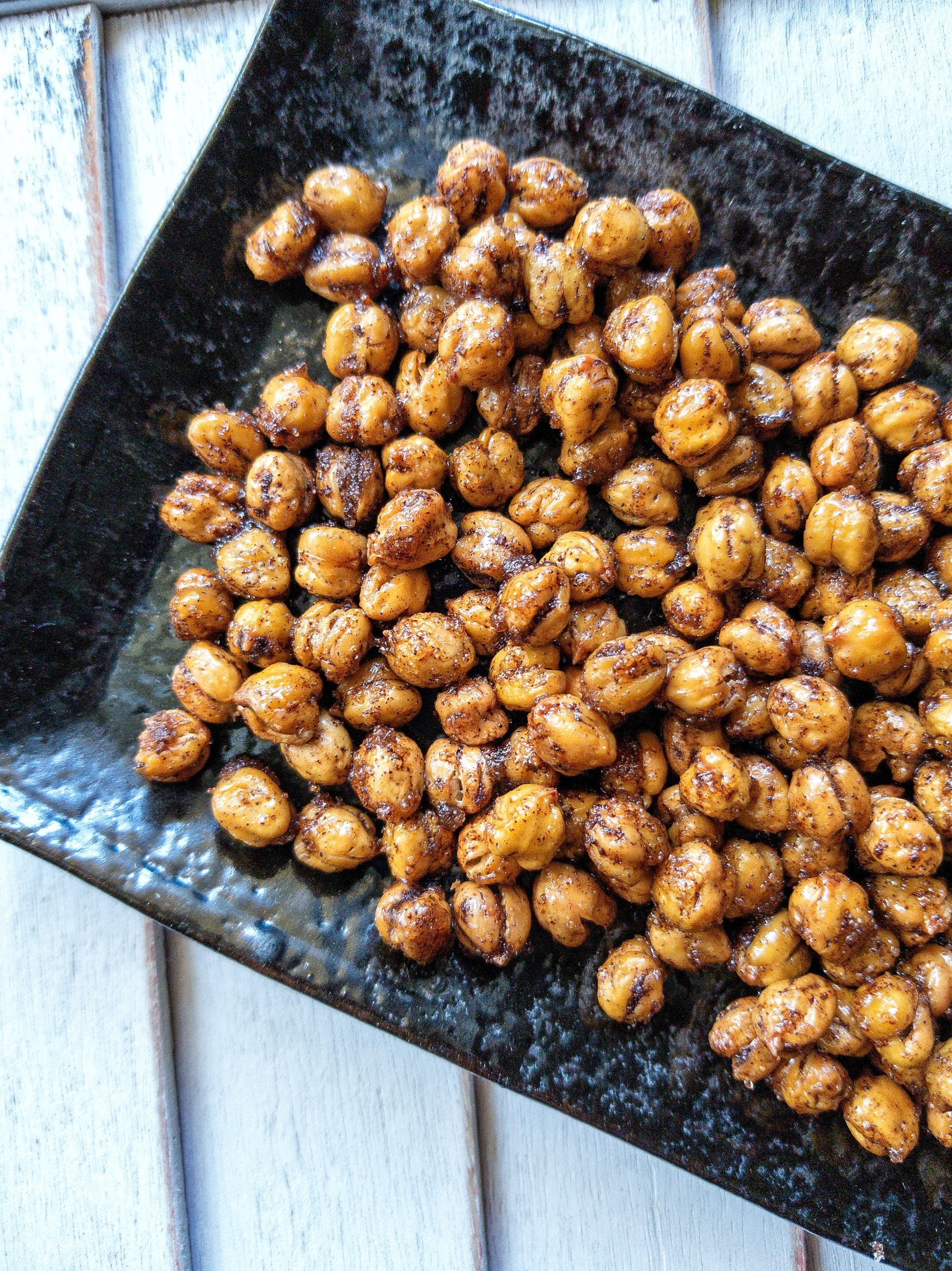 Roasted chickpeas with cinnamon on a small, black platter