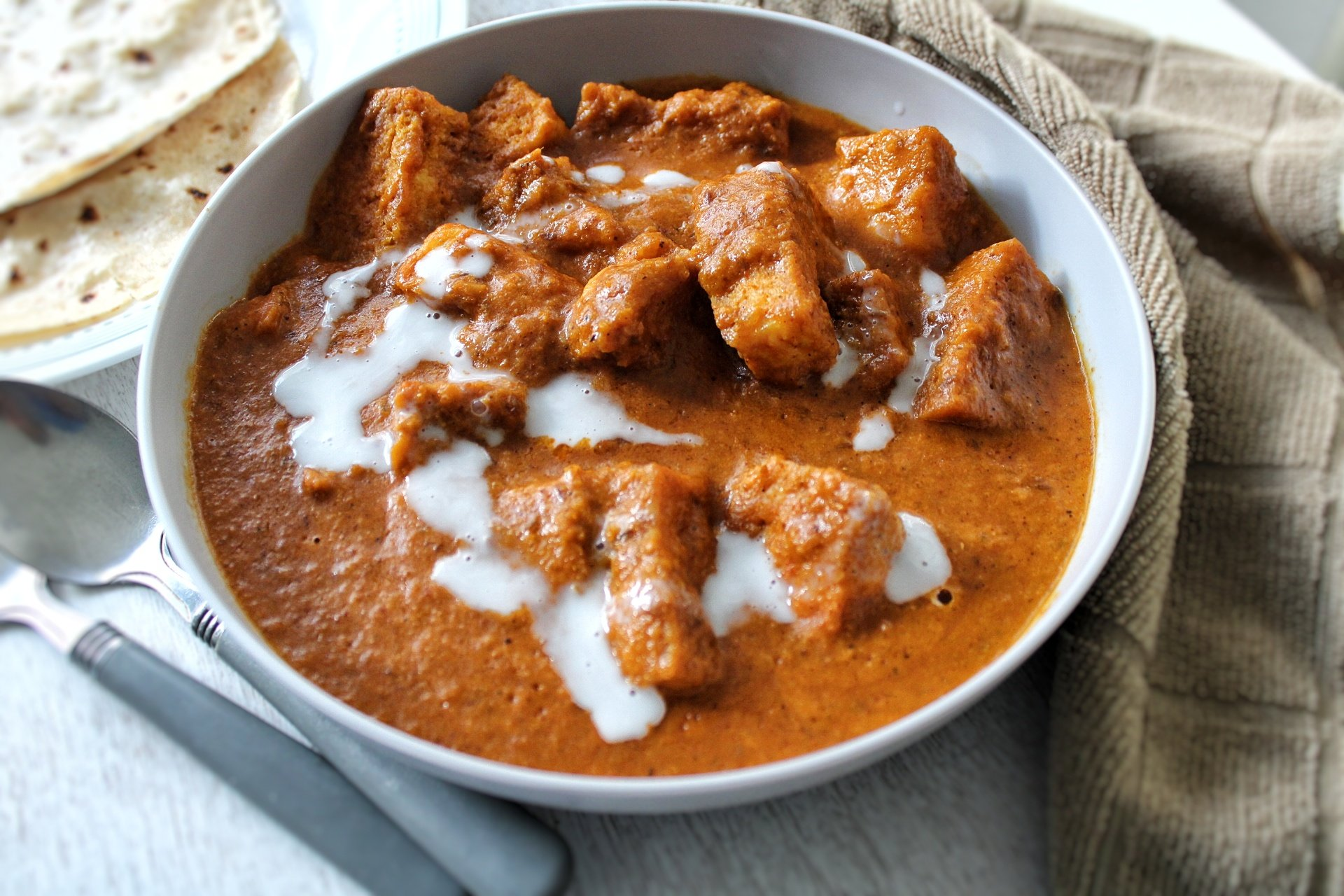 Meatless butter chicken in a gray bowl and side of roti