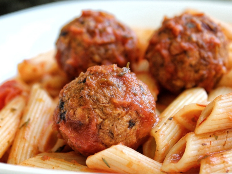 Vegan lentil meatballs tossed in sauce and served with penne pasta