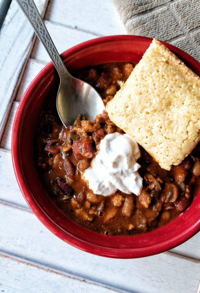 Bowl filled with vegan chili topped with vegan sour cream and cornbread