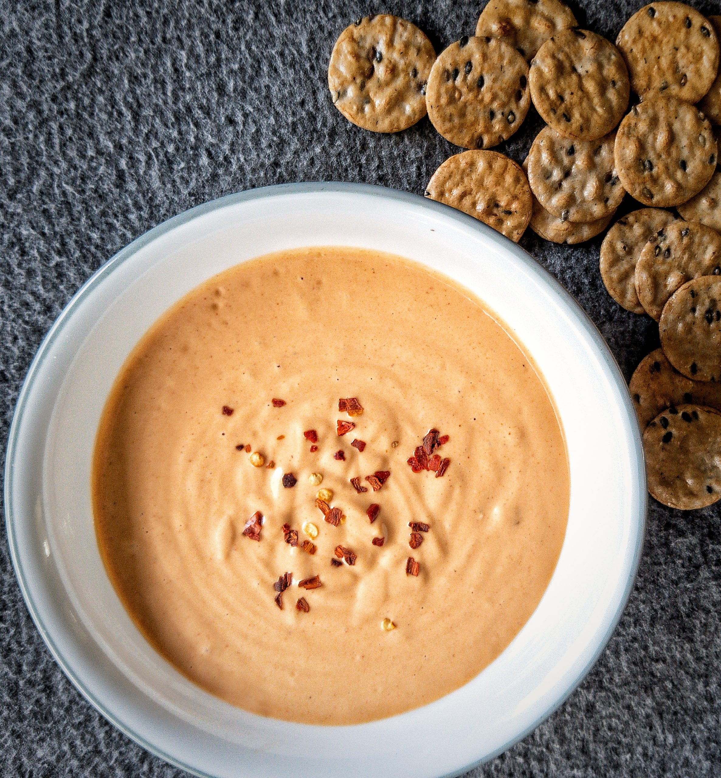 Cashew-based cheese sauce in a white bowl topped with a side of crackers