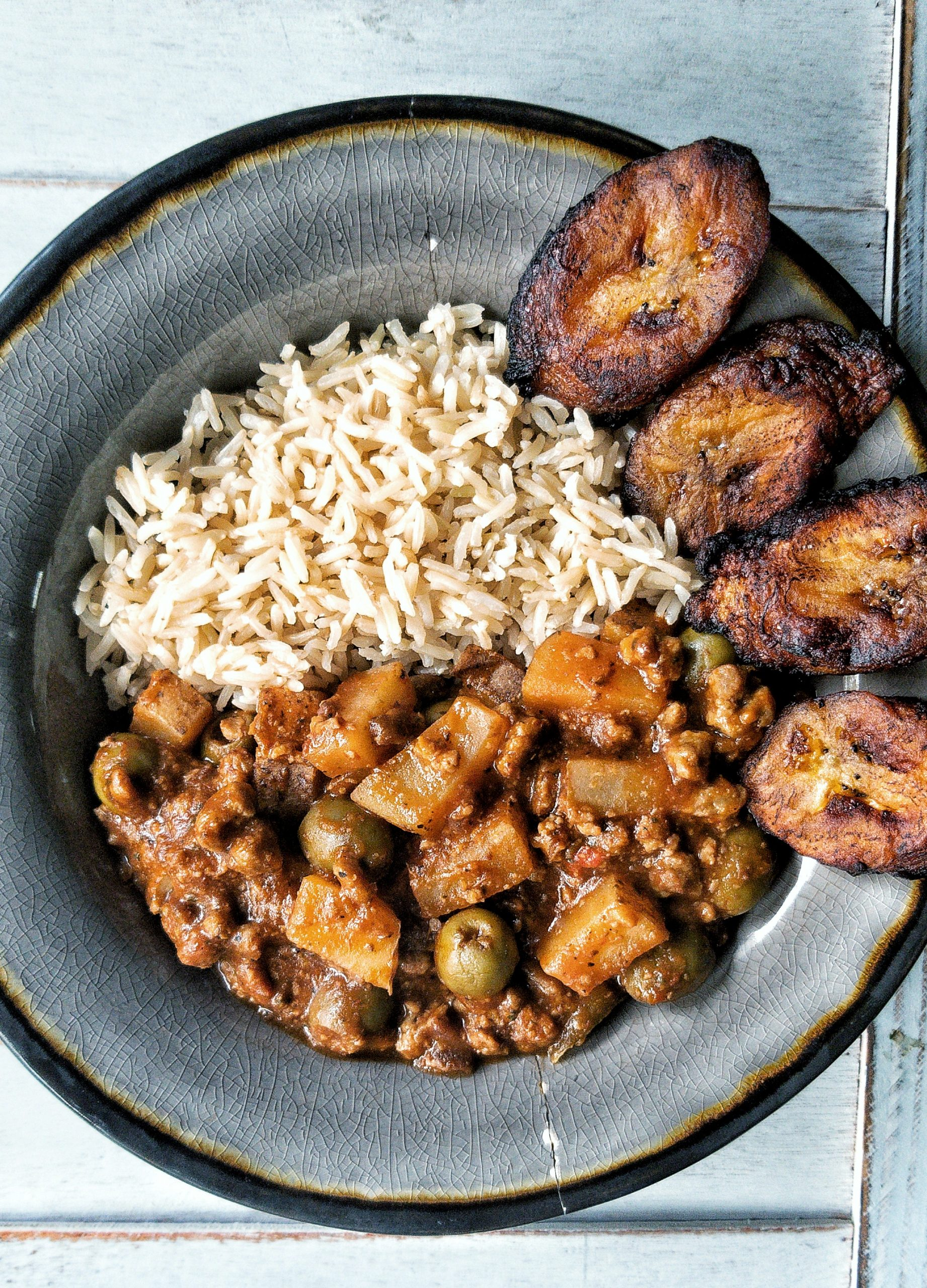 Vegan picadillo in a bowl with brown rice and sweet, fried plantains
