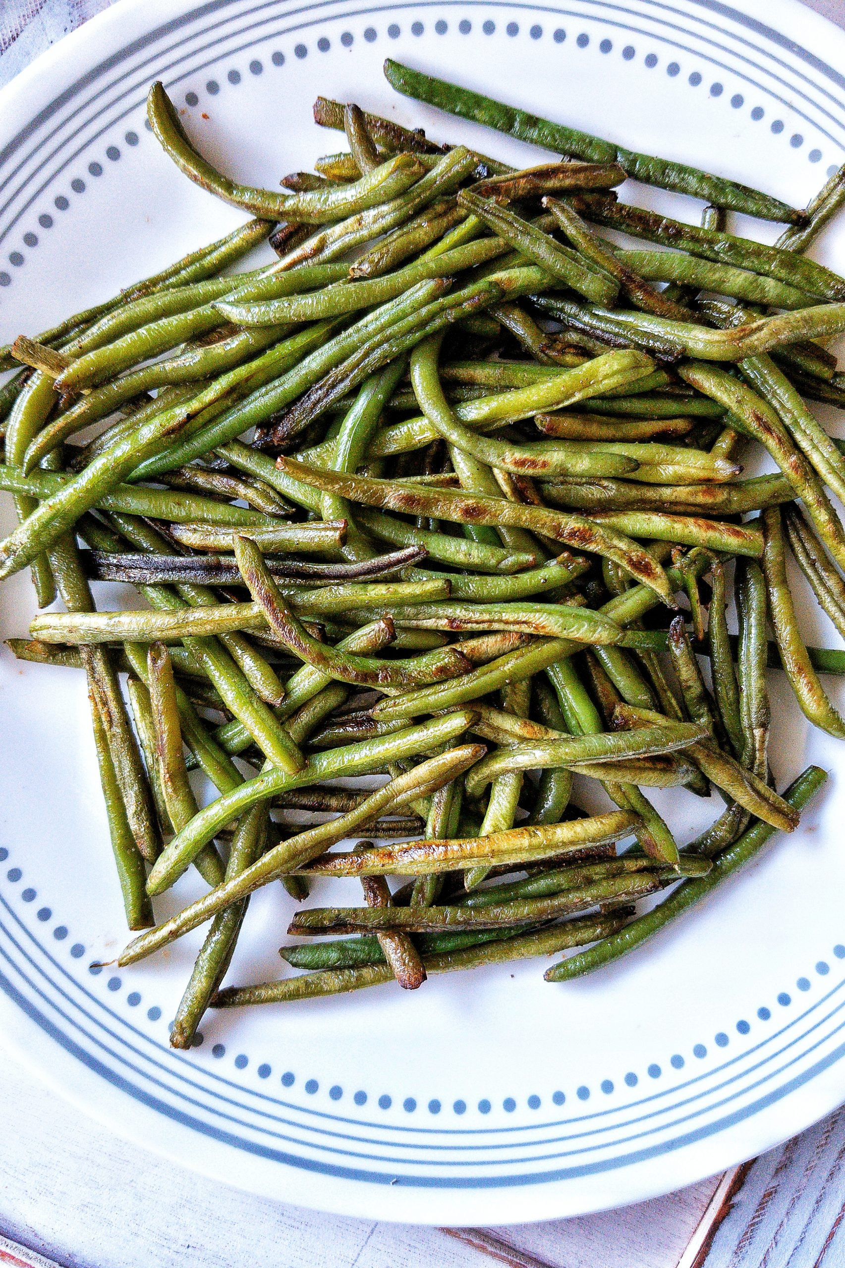 Blistered green beans on a white plate