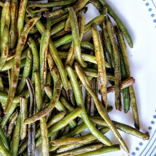 Pan-fried blistered green beans on a plate