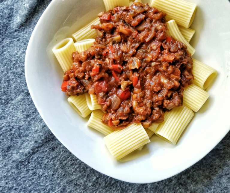Vegan bolognese sauce, or meat sauce on top of cooked pasta.