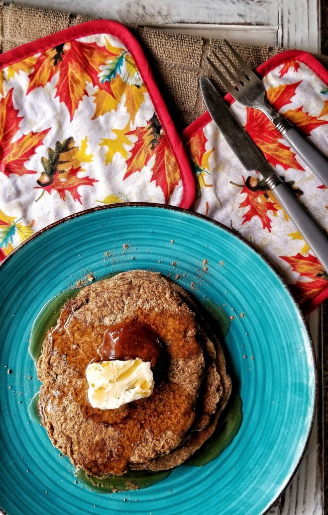 Spiced gluten-free pancakes topped wit hpantry syrup and vegan butter.