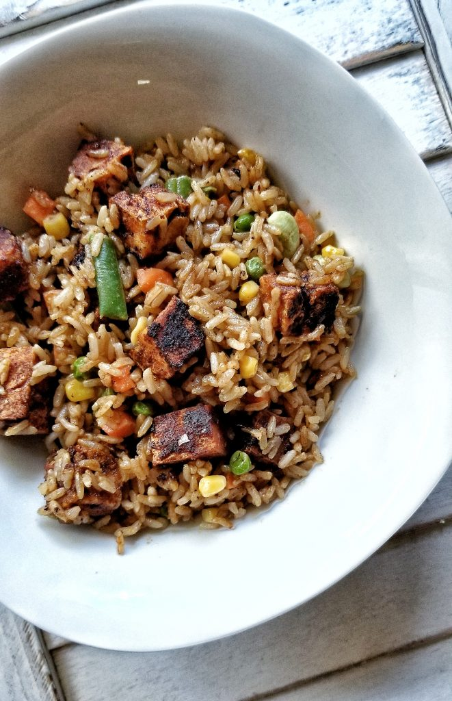 "Bowl of stir-fried brown rice with mixed vegetables and tofu ""chicken"""