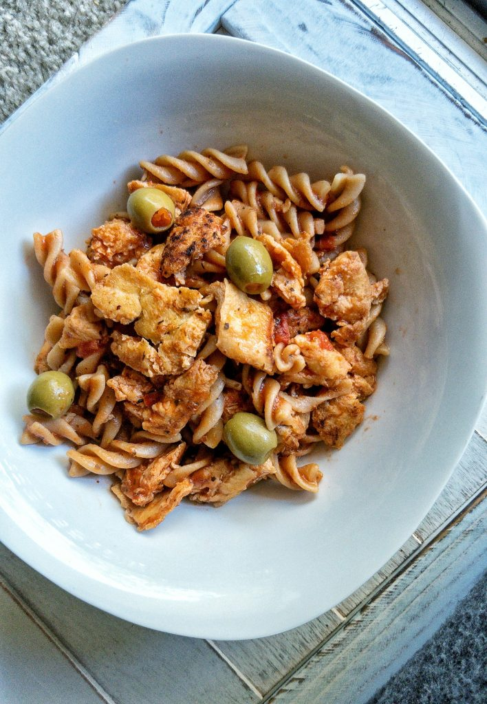 Bowl of spiral pasta with olives and tofu chicken