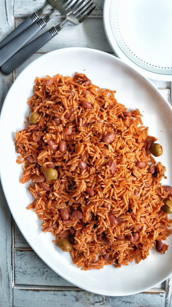 Seasoned Puerto Rican yellow rice with red beans, Spanish olives, tomato sauce on a large plate