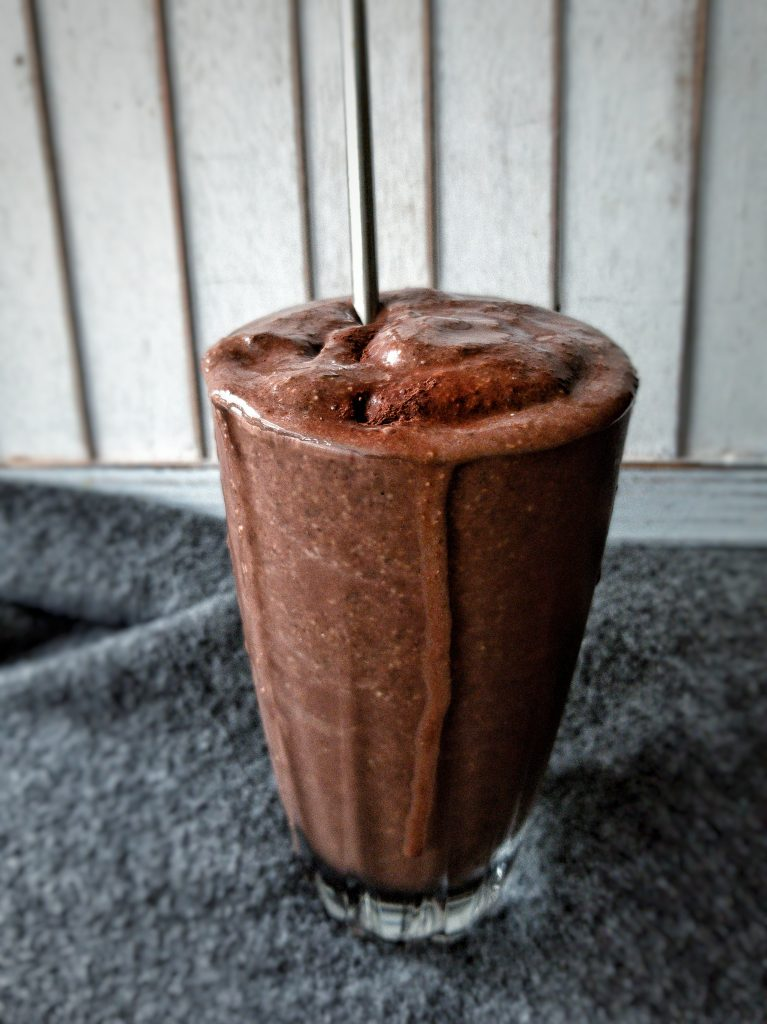 chocolate peanut butter smoothie in a glass cup with a straw