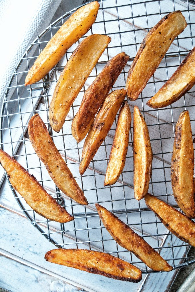 Crispy potato wedges snack baked in the oven and seasoned with salt