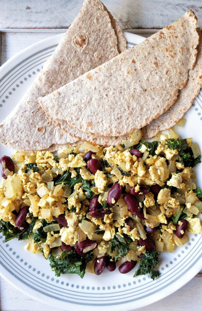 Less or fewer than 10 ingredients loaded tofu scramble with kale, beans veggies, and warm tortillas
