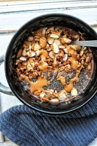 A chocolate banana smoothie bowl topped with peanut butter, chia seeds, sliced almonds, and granola