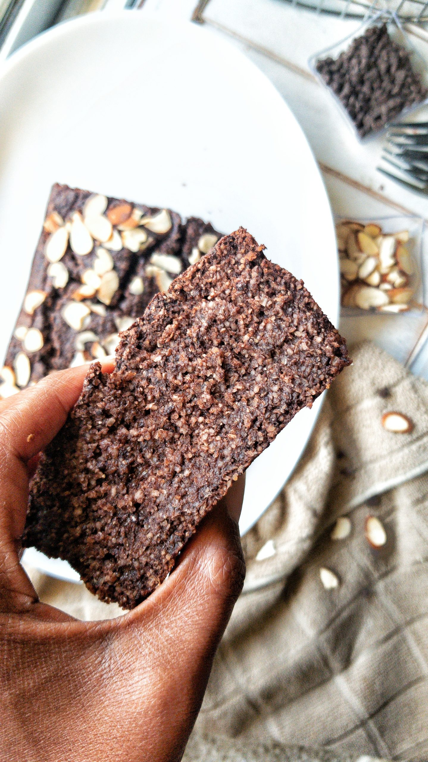 A close-up slice of plant-based, Gluten-Free Double Chocolate Banana Bread topped with almonds.