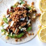 Flour tortilla topped with vegetables and walnut meat with a side of sliced lemon