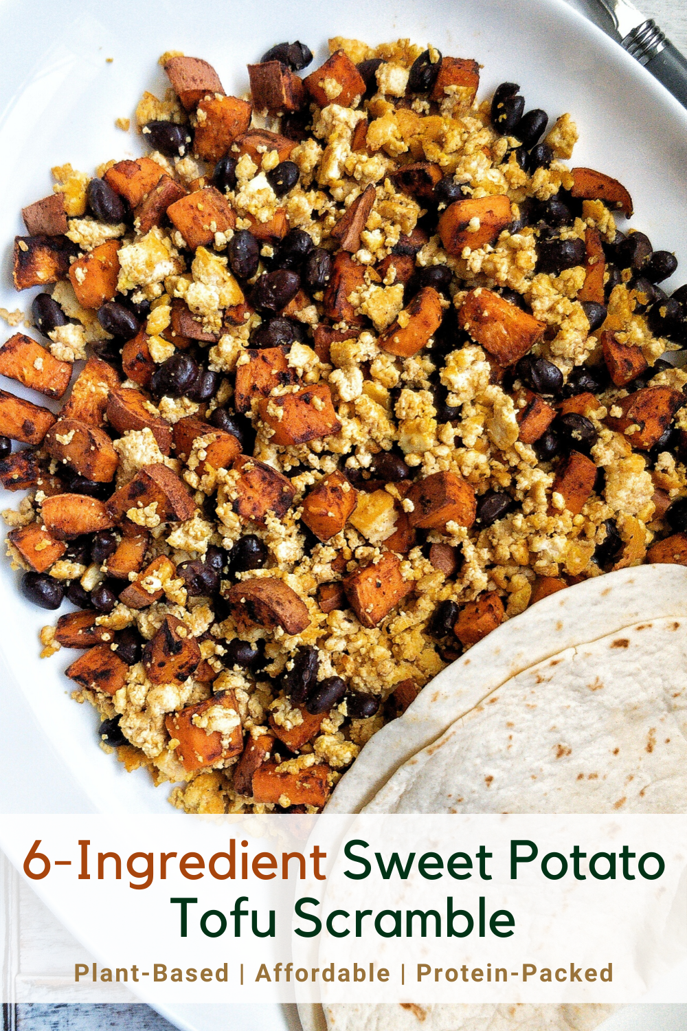 A platter with tofu scramble loaded with sweet potato, black beans, and a side of tortillas