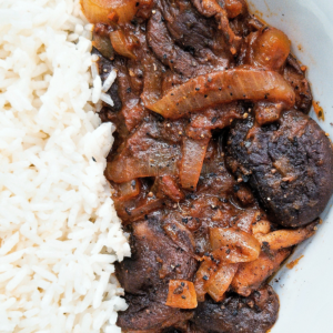 Stewed mushrooms with onions on a plate with a side of rice.