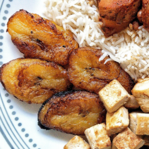 A plate with sweet fried plantains, rice, and tofu.