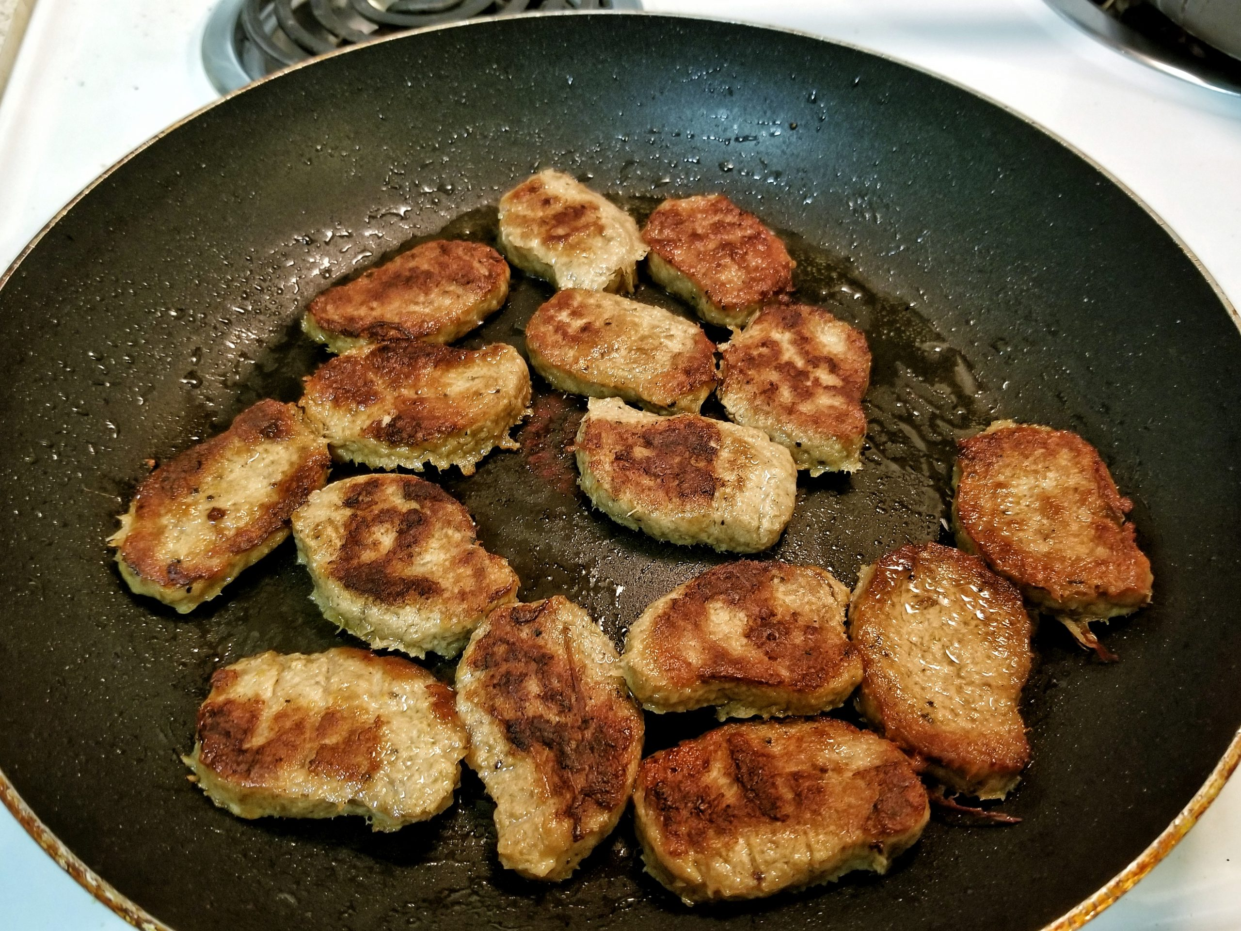 Mock meat nuggets cooking in a large non-stick pan