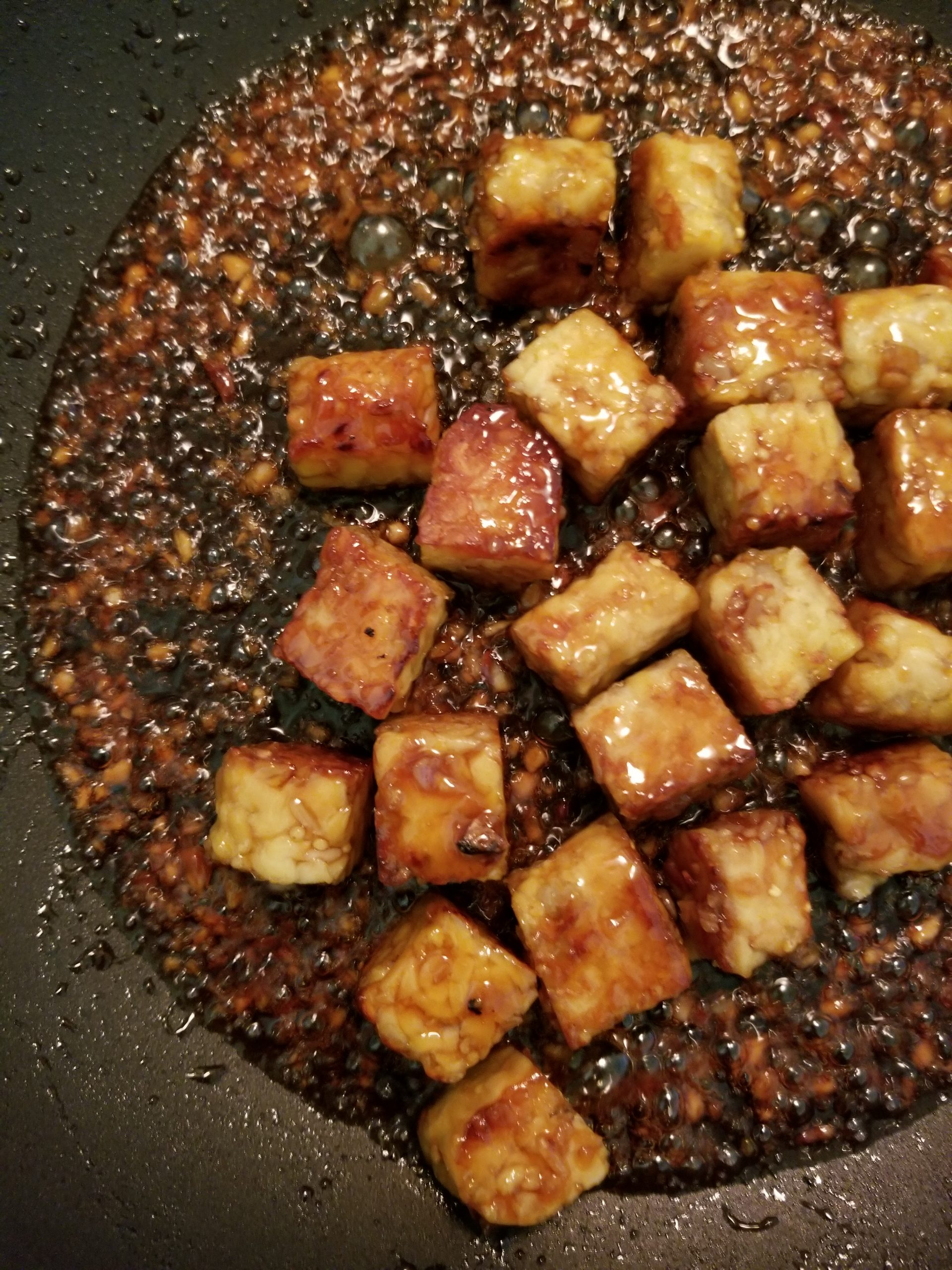 Chopped tempeh cubes stir-fried and cooked in a honey garlic sauce
