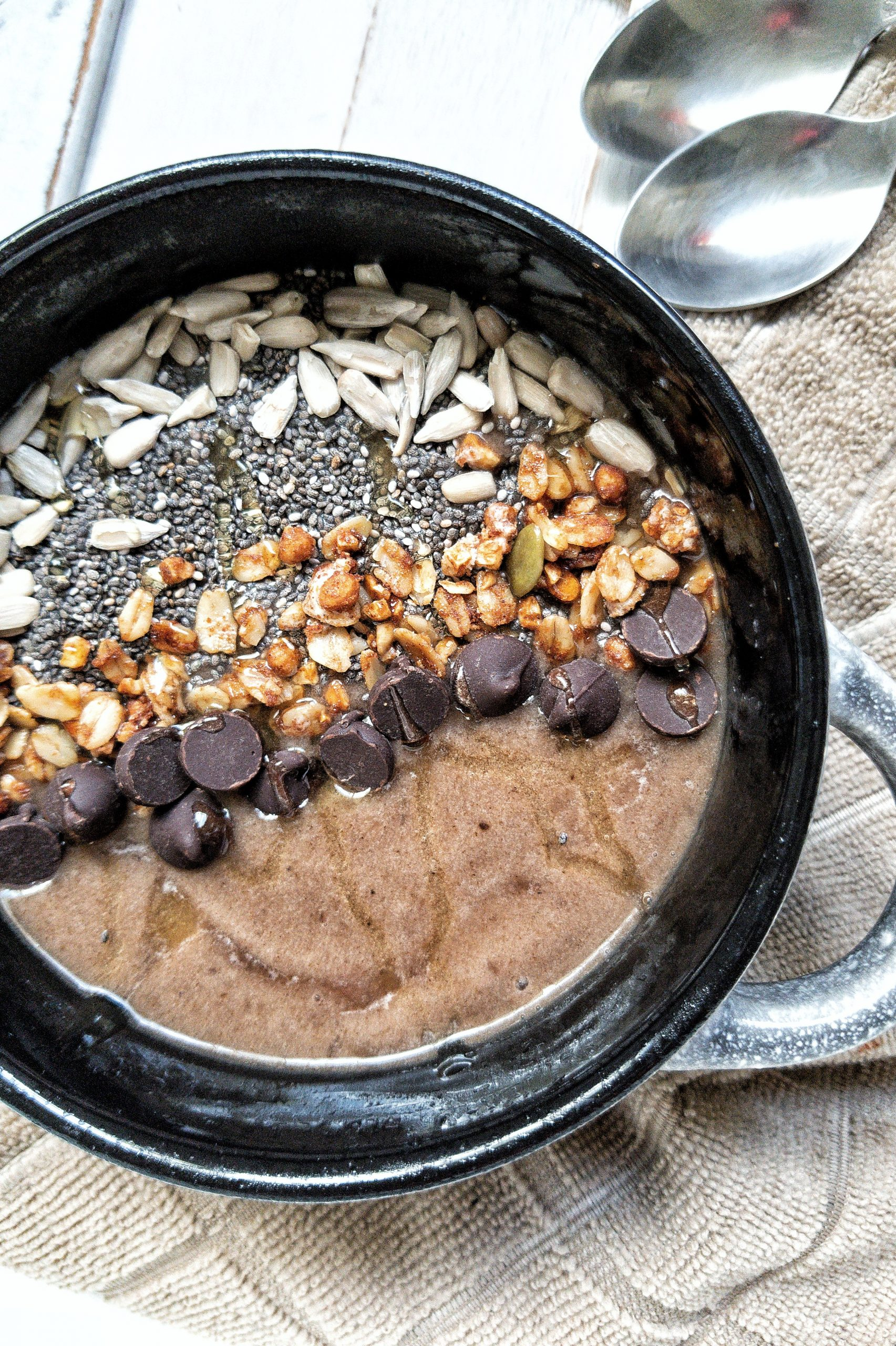 A coffee smoothie bowl topped with raw sunflower seeds, chia seeds, ganola, chocolate chip, and a drizzle of honey