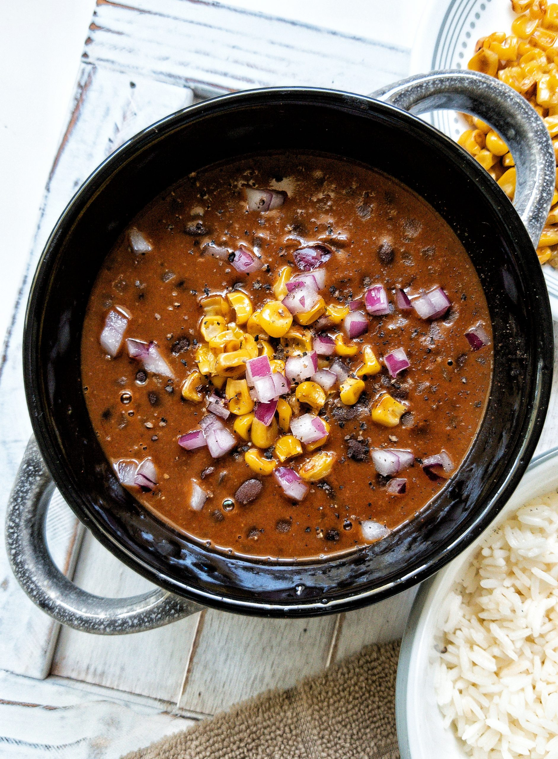Black bean soup in a black bowl topped with pan-roasted corn, chopped red onions, and cracked black pepper