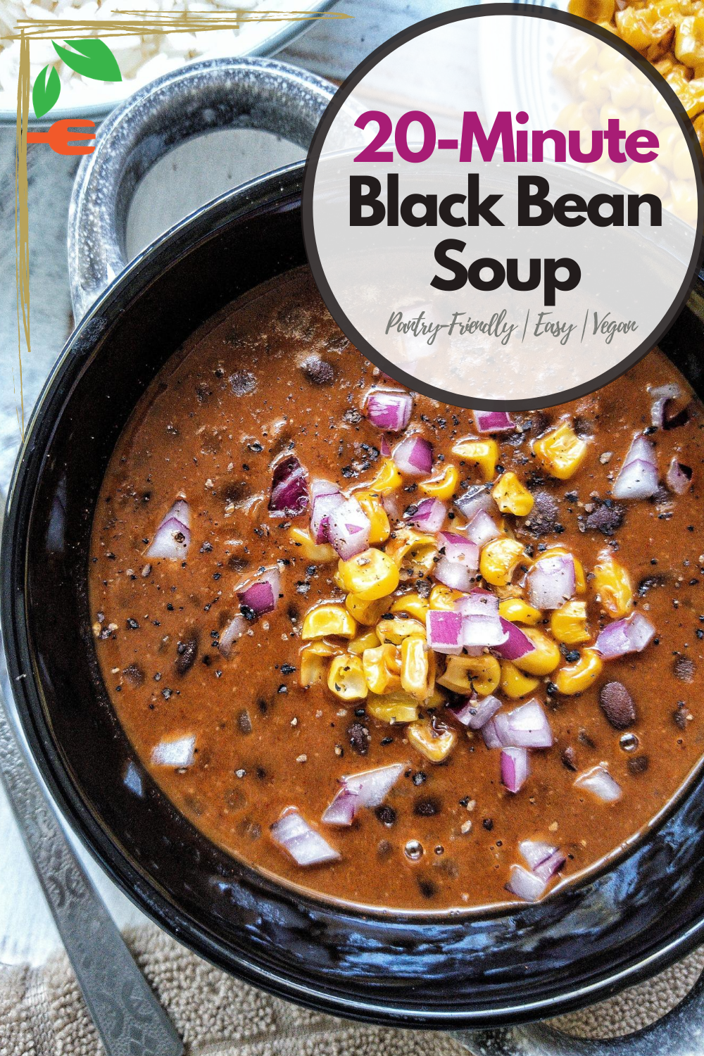 Bowl of black bean soup topped with red chopped onions and pan-roasted corn