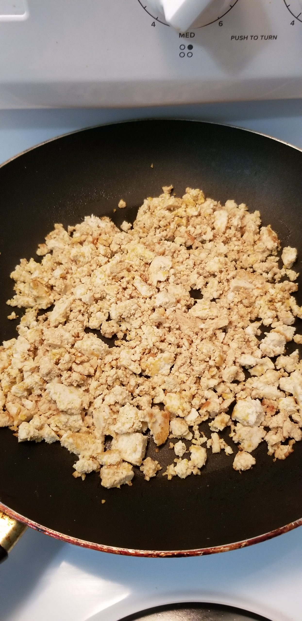 Close up of pan-fried, crumble tofu with soy suace and nutritional yeast.