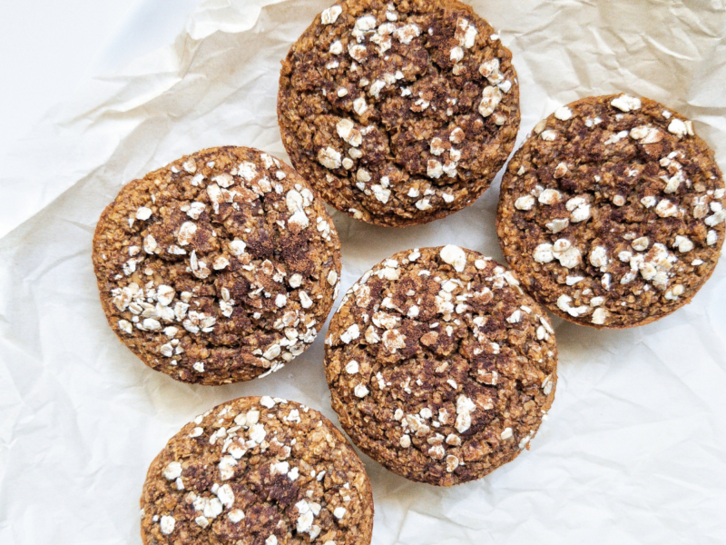 Five fluffy chia seed pumpkin muffins on parchment paper