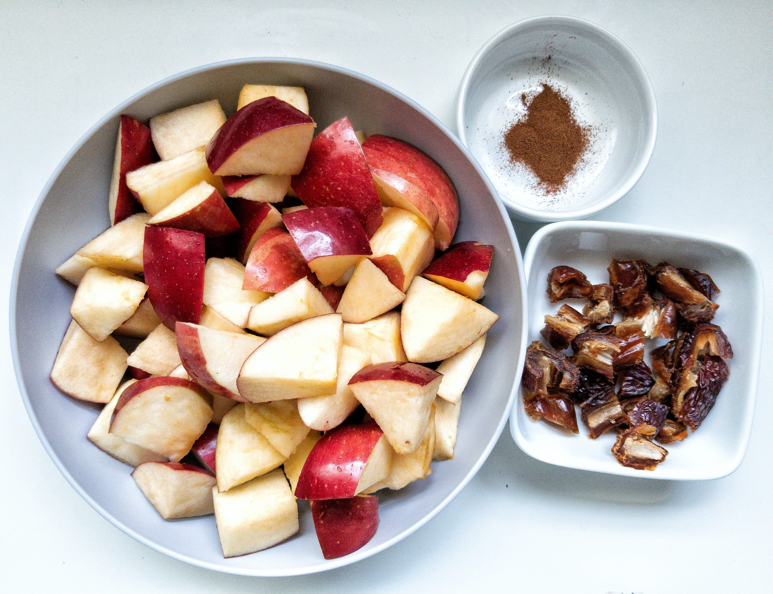 Chopped apples in a bowl with a side of dates and ground cinnamon