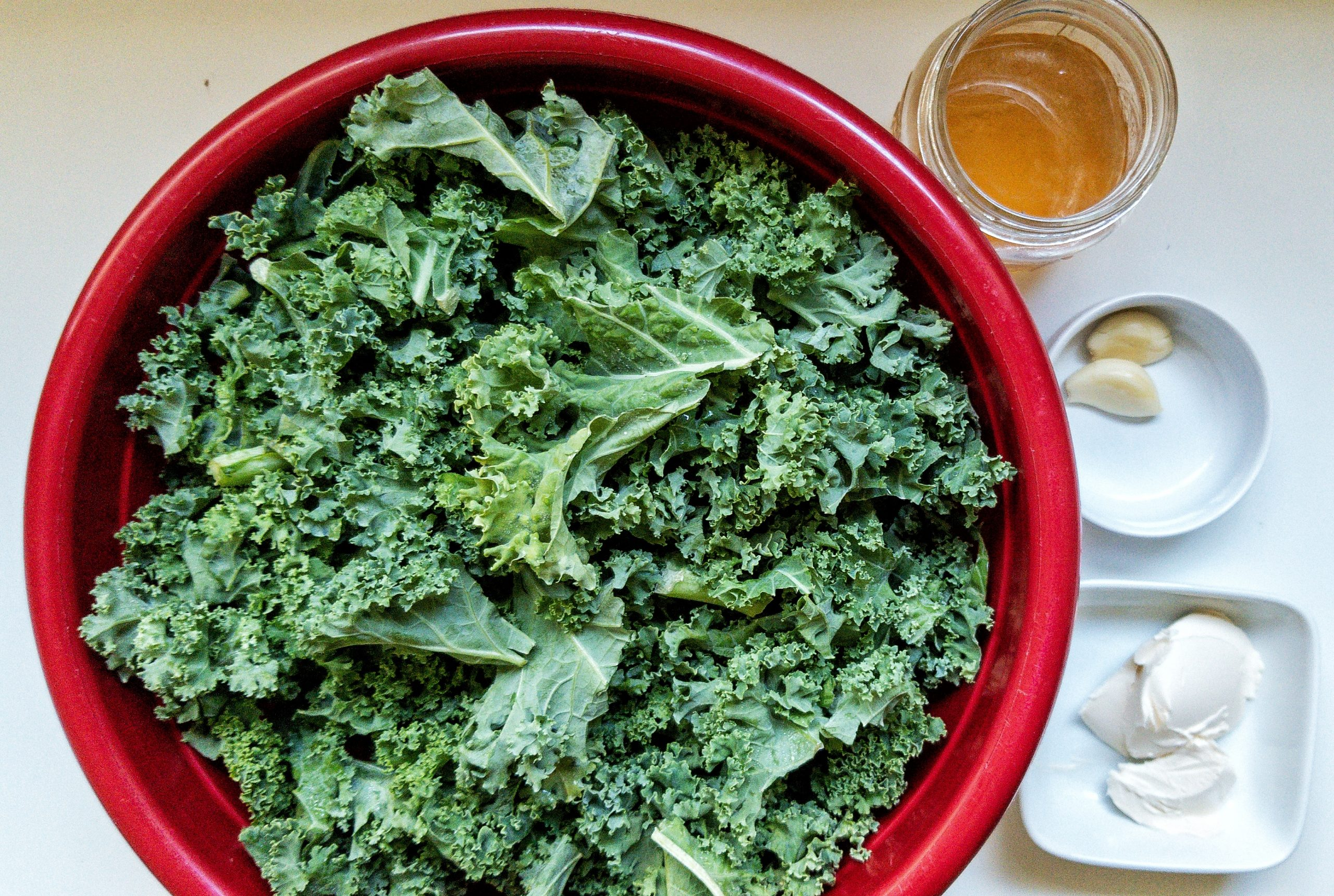 Large bowl of raw kale in a large mixing bowl with measured vegan butter, garlic, and vegetable stock