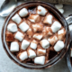 Coconut hot chocolate in a clear, glass mug topped with vegan marshmallows