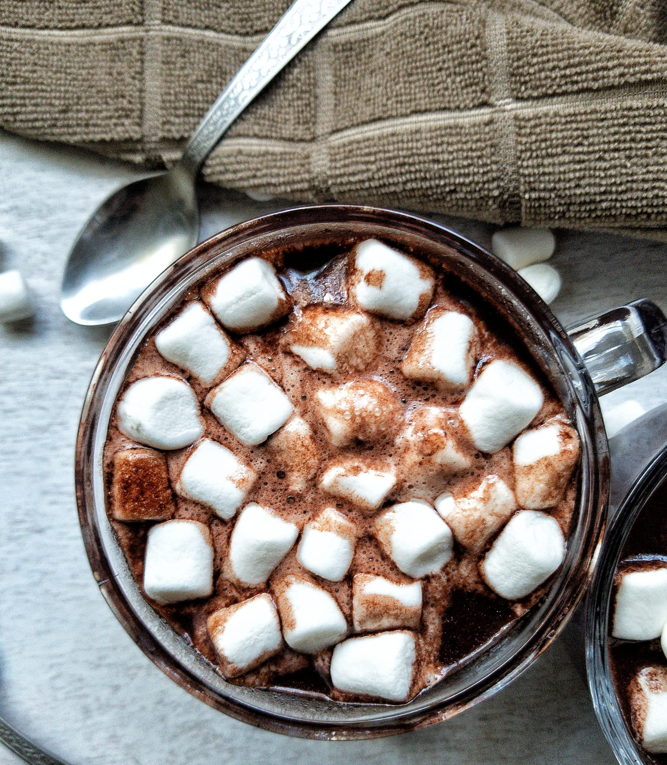 Close-up of one glass mug with hot chocolate topped with marshmallows