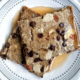 Square-shaped, sheet-pan pancakes with chocolate chips and sliced almonds and a drizzle of pancake syrup